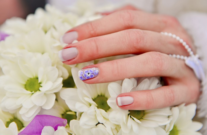 Bride hands manicure on the white bouquet